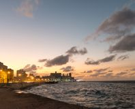 Sunset at Malecon, the famous Havana promenades. Cuba. At the bo. Sunset at Malecon, the famous Havana promenades where Habaneros, lovers and most of all Royalty Free Stock Photography