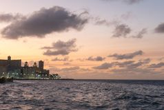 Sunset at Malecon, the famous Havana promenades. Cuba. At the bo. Sunset at Malecon, the famous Havana promenades where Habaneros, lovers and most of all Royalty Free Stock Photo