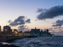 Sunset at Malecon, the famous Havana promenades. Cuba. At the bo. Sunset at Malecon, the famous Havana promenades where Habaneros, lovers and most of all Royalty Free Stock Image