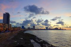 Sunset at Malecon, the famous Havana promenades where Habaneros, lovers and most of all individual fishermen meet, Havana, Cuba. Sunset at Malecon in Havana Stock Photo