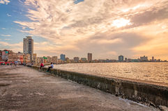Sunset at Malecon, Old Havana, Cuba. Havana, Cuba - March 6, 2016: Sunset at the sea shore promenade called Malecon in Old Havana, Cuba Stock Image