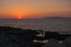 Sunset in Malta. Red sunset in Malta with silhouette of the islands Gozo and Comino Royalty Free Stock Photography