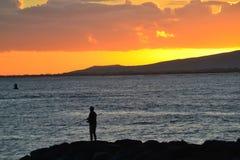 Sunset. Man fishiing off the rocks atala-moana beach Honolulu hawaii Stock Image