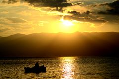 Sunset. A man on the little boat is enjoying with the perfect view. Mountain,clouds and pretty yellow colour is what he needs Stock Photography
