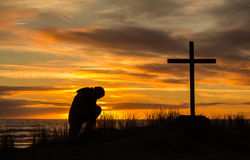 Sunset Man Of Prayer. Beautiful sunset as man bows down to pray God before a cross Royalty Free Stock Photos