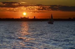 Sunset in Manhattan Bay. The silhouette of Ellis Island and the vessels against the sunset Royalty Free Stock Image