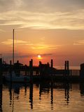 Sunset Marina. Summer sunset over a maritime marina. A lone sailboat docked casts a reflection in the rippling water Stock Images