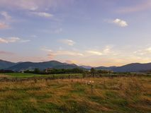 Sunset meadow. Beautiful sunset meadow with colorful clouds and mountains in the background and wooden fence stock images