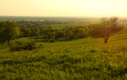 Sunset Meadow with Path to Distant Village Royalty Free Stock Images