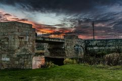 Sunset in the medieval city. Medieval bridge under fiery sky royalty free stock image
