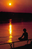 Sunset meditation. Meditation on a sunset river Royalty Free Stock Photo