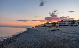 Sunset on a Mediterranean beach of Ionian Sea with Mount Etna Volcano on background - Bova Marina, Calabria, Italy Royalty Free Stock Photography