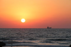 Sunset in the Mediterranean sea, a boat on the horizon. Sunset in the Mediterranean sea, a ship on the horizon far from the coast, waves Royalty Free Stock Photos