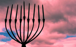 Sunset Menorah. A silhouette of a candled menorah against a sunset sky Royalty Free Stock Image