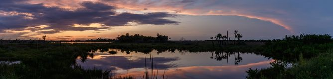 Sunset at Merritt Island National Wildlife Refuge, Florida. Sunset with clouds reflecting in a pond at Merritt Island National Wildlife Refuge, Florida, USA stock image