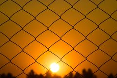 Sunset with Metallic Nets in front Background Photograph. The beautiful sunset with dark trees and metallic nets abstract object photograph Stock Images