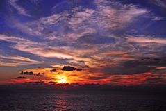 Sunset Moment at Sea. A sunset at sea illuminates low hanging clouds over the ocean Royalty Free Stock Photography