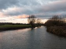 sunset moody sky winter autumn over green field with trees water Stock Photo