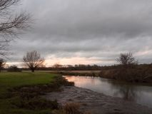 sunset moody sky winter autumn over green field with trees water Royalty Free Stock Photography