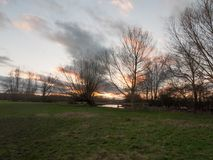 sunset moody sky winter autumn over green field with trees water Royalty Free Stock Photo
