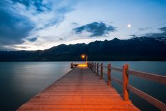 Moon rising at Glenorchy Wharf, NZ. After sunset, the moon is rising at Glenorchy Warf. Glenorchy is a charming touristic village situated at the Northern end of Royalty Free Stock Photography
