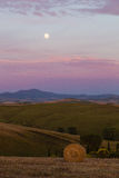 Sunset with moon. On the Tuscan hills Stock Image