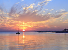 Sunset Mooring. The silhouette of a sailboat moored in English Navy Cove off Gulf Breeze, Florida at Sunset Stock Image