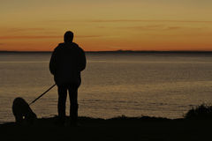 Sunset Mornington, Victoria. Sunset behind You Yangs across Port PhillipBay in Mornington. silhouette of a man and his dog Royalty Free Stock Photography