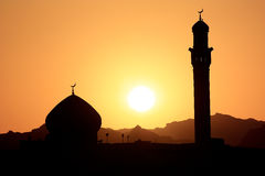 Sunset and mosque. The black siluette of mosque domes in Oman Royalty Free Stock Photos