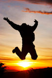 Sunset in mountain. Hiker jumps at the sunset on mountain stock images
