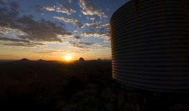 Sunset on a mountain beside a rustic water tank. Sunset sky landscape atop a mountain with a rustic water tank in the foreground of the Glasshouse Mountains in stock photo