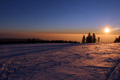 Sunset in mountains and fog in wintertime Stock Image