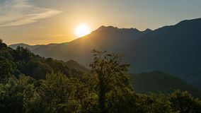 Sunset in the mountains among the green trees stock photos