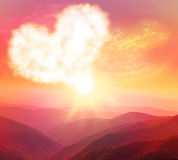 Sunset in the mountains. Heart on a background of a sunset in the mountains royalty free stock photo