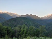 Sunset in the mountains. Of Krasnaya Polyana, Sochi. June landscape. Stormy summer vegetation and the last snow on the mountain tops royalty free stock photos