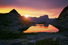 Sunset in mountains near lake. Sunlight reflected on mountain tops. Golden light from sky reflected in a mountain lake. Ergaki. Stock Photo