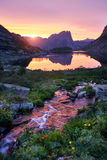Sunset in mountains near river. Sunlight reflected on mountain tops. Golden light from sky reflected in a mountain river. Ergaki. Royalty Free Stock Photography