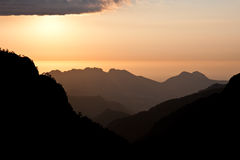 Sunset in mountains near seashore Stock Images