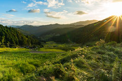 Sunset in the mountains with rice paddy fields and forest. Sun rays beaming over mountain peak with lens flare visible. Yotsuya, Aichi prefecture, Japan Stock Photography