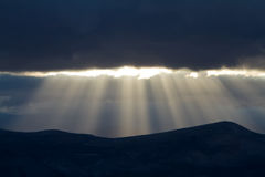 Sunset in mountains with sunbeams. On the dark sky background stock photo