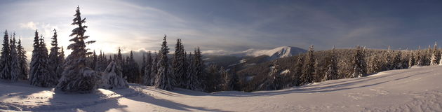 Sunset in the mountains. Winter day in the snowy mountains with a sunset. Widescreen picture Royalty Free Stock Image