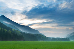 Sunset in mystical mountain meadow landscape Royalty Free Stock Photography