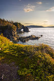 Sunset with a natural bridge. In view along a coastal area of Green Bay near Langdon`s Cove, Newfoundland & Labrador Stock Images