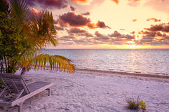 Sunset in a natural Maldivian beach. Empty chair in the tropical beach in the Maldives at sunset royalty free stock image