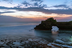 Sunset near famous tourist landmark of Bali island - Tanah Lot & Batu Bolong temple. Royalty Free Stock Image