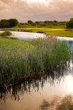Sunset near Golf Course. A view of the water and marsh near a golf course. The dramatic sky and reflections give a peaceful feeling stock photos