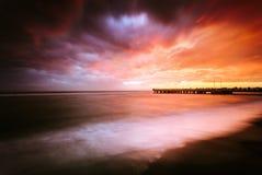 Sunset near a pier on the beach in Ostia Stock Image
