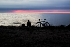 Sunset Near The Sea And People With Bicycle Silhouette. In Beautiful Evening royalty free stock images