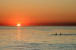 Sunset in the Netherlands. Two persons are bathing in the IJsselmeer during sunset in Urk (the Netherlands Royalty Free Stock Images