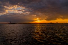 Sunset at New York Harbor. Spectacular sunset view of New York Harbor with sight of Statue of Liberty in the distance Royalty Free Stock Photo